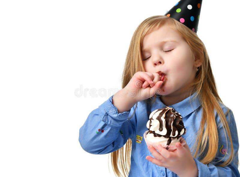 Três anos de criança da menina comem o bolo de chocolate doce que comemora no tampão do aniversário isolado fotos de stock