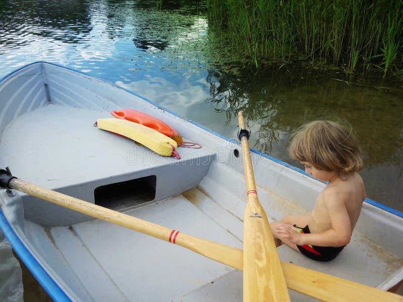 Três anos de menino idoso em um barco imagens de stock royalty free