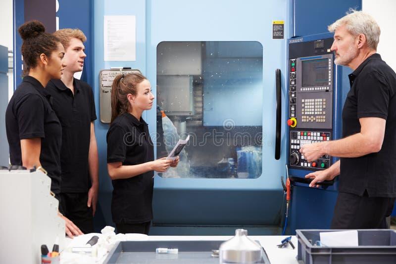 Três aprendizes que trabalham com maquinaria do CNC de On do coordenador fotos de stock