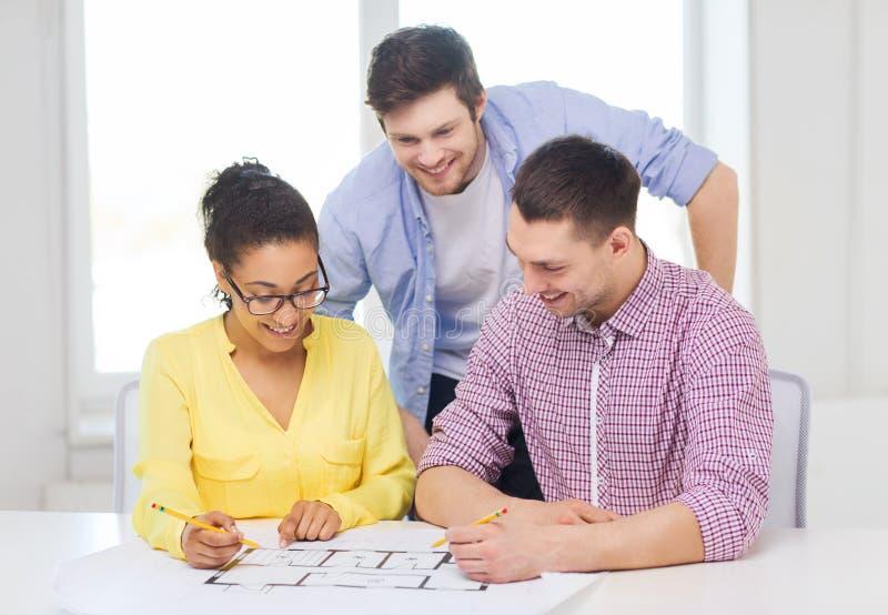 Três arquitetos de sorriso que trabalham no escritório foto de stock royalty free