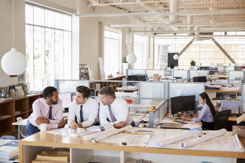 Três arquitetos masculinos na discussão em um escritório de plano aberto fotografia de stock royalty free