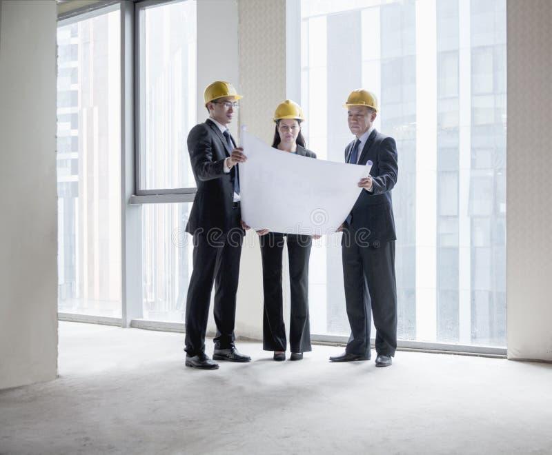 Três arquitetos nos capacete de segurança que examinam um modelo em um prédio de escritórios foto de stock royalty free