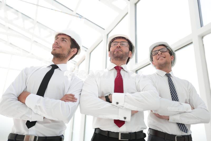 Três arquitetos que estão em um escritório vazio imagens de stock