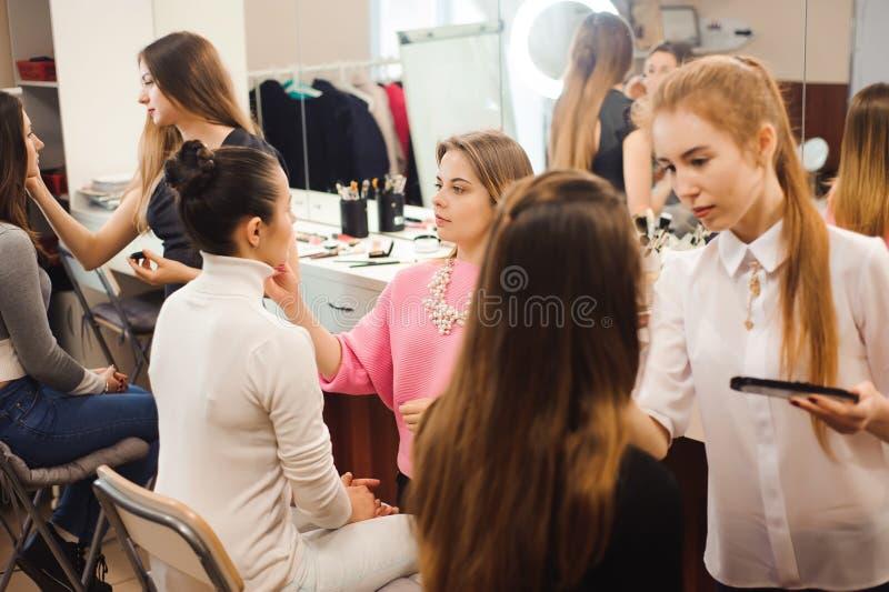 Três artistas de composição profissionais trabalham com jovens mulheres bonitas Escola da composição profissional fotos de stock