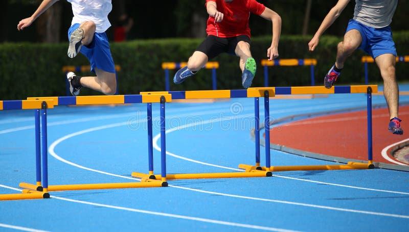 Três atletas novos ao correr obstáculos na pista de atletismo imagem de stock royalty free
