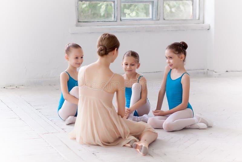 Três bailarinas pequenas que dançam com o professor pessoal do bailado no estúdio da dança fotografia de stock