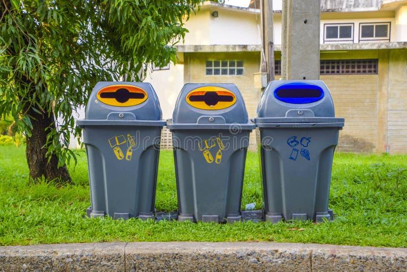 Três baldes do lixo cinzentos situados ao longo do trajeto no parque, lixo de jogo no lixo, ajuda para manter-se por favor limpo  fotos de stock