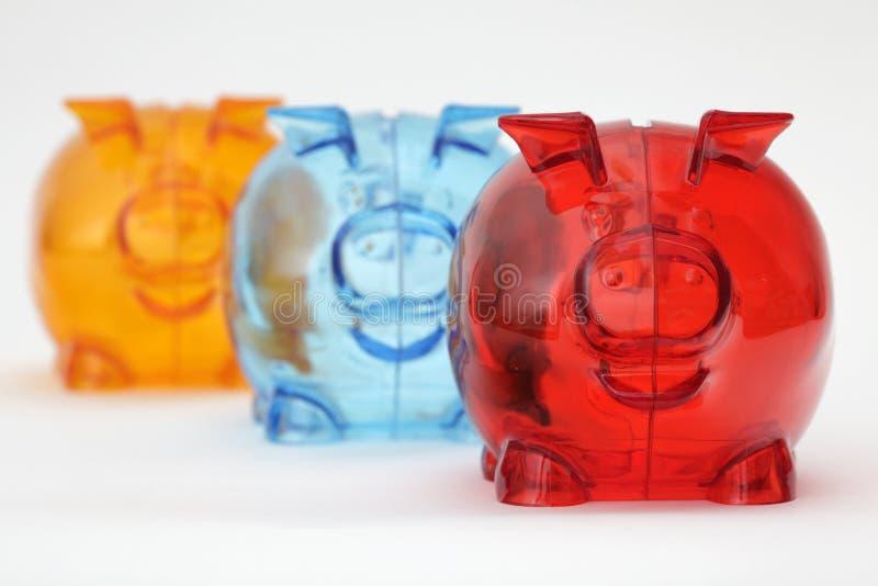 Três bancos piggy coloridos em uma fileira imagens de stock royalty free