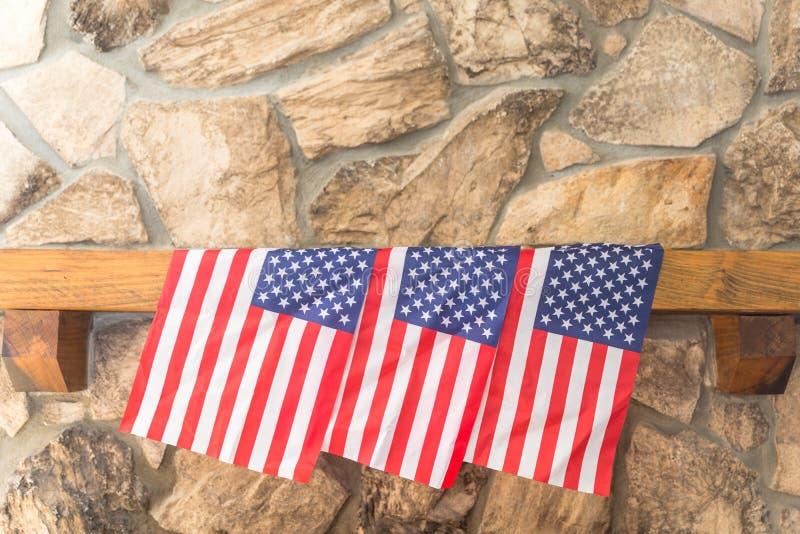 Três bandeiras americanas em um envoltório da chaminé de pedra fotografia de stock