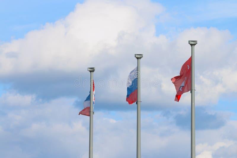 Três bandeiras em polos e céu - bandeira de Rússia, bandeira da cidade do permanente imagem de stock