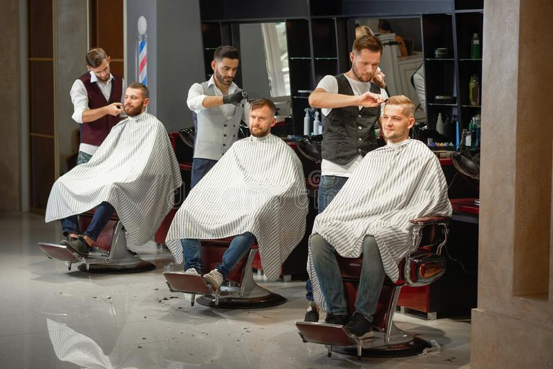 Três barbeiros que fazem a denominação do cabelo e da barba na barbearia fotos de stock