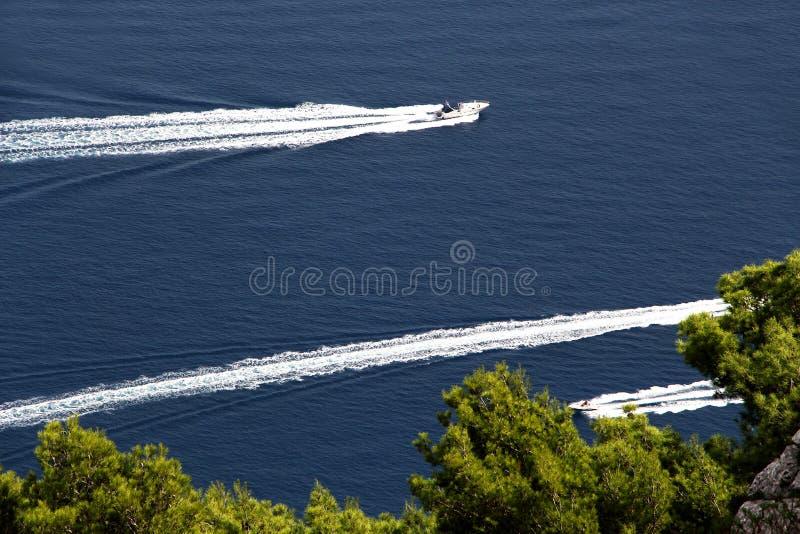 Três barcos a motor contra um mar azul e árvores imagem de stock