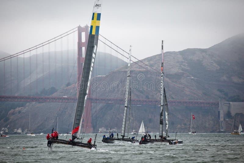 Três barcos que competem no copo de Louis Vuitton competem nos Americas as séries do copo que navegam na frente de golden gate bri foto de stock royalty free