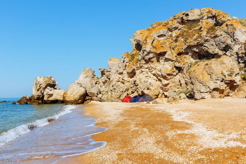 Três barracas em um litoral selvagem Ideia do acampamento da água fotografia de stock