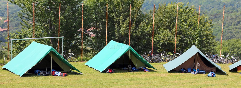 Três barracas verdes montaram por escuteiros em um prado fotos de stock royalty free