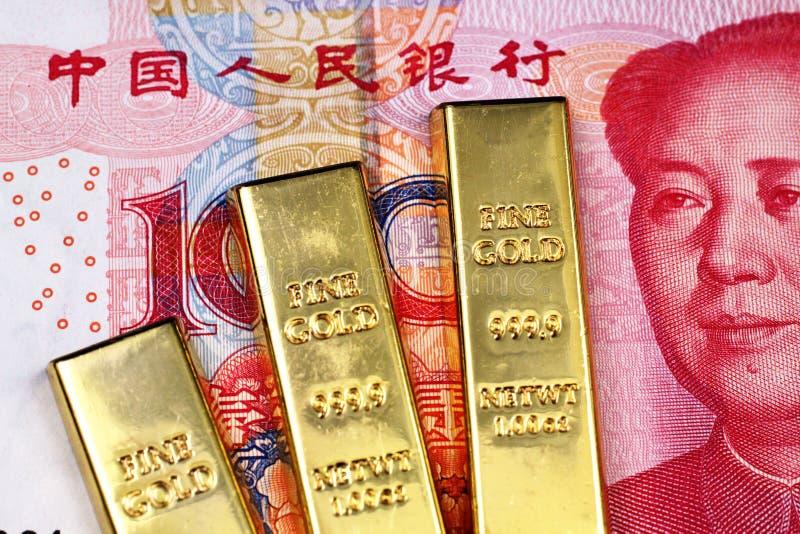 Três barras de ouro pequenas com 100 vermelhos um fim chinês da cédula do yuan acima fotos de stock