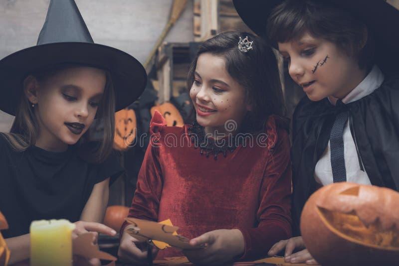 Três bastões cortados crianças para um partido de Dia das Bruxas Crianças vestidas nos trajes dos monstro imagem de stock
