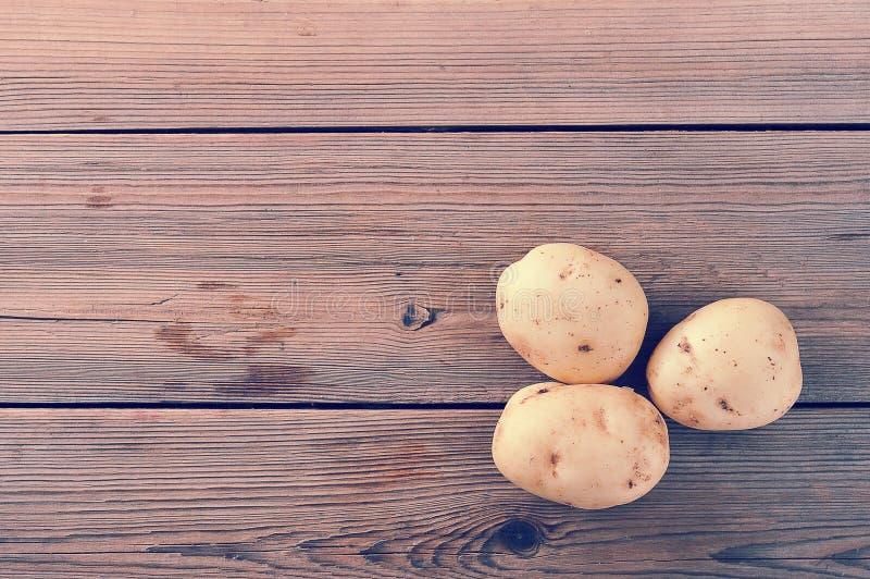 Três batatas brancas cruas do tubérculo novo no fundo de madeira rústico imagens de stock