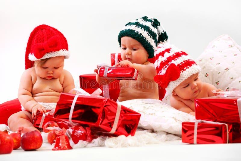 Três bebês nos trajes do xmas que jogam com presentes fotografia de stock royalty free