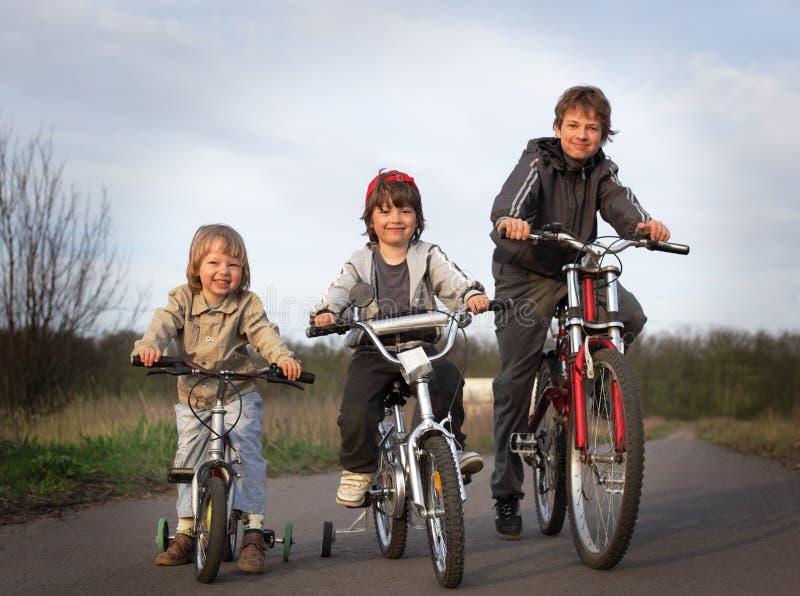 Três bicicletas do passeio dos irmãos foto de stock royalty free