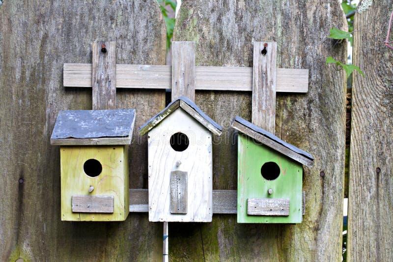 Três birdhouses na cerca de madeira velha imagem de stock