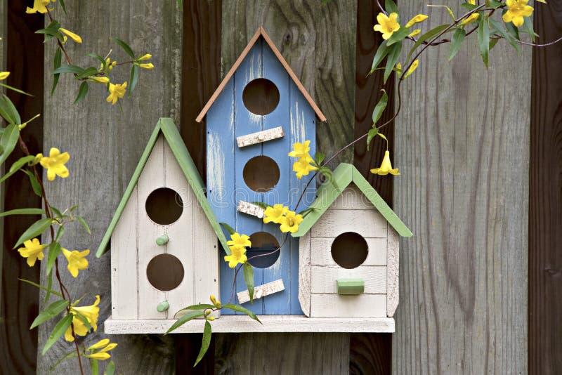 Três birdhouses pequenos bonitos na cerca de madeira com flores foto de stock