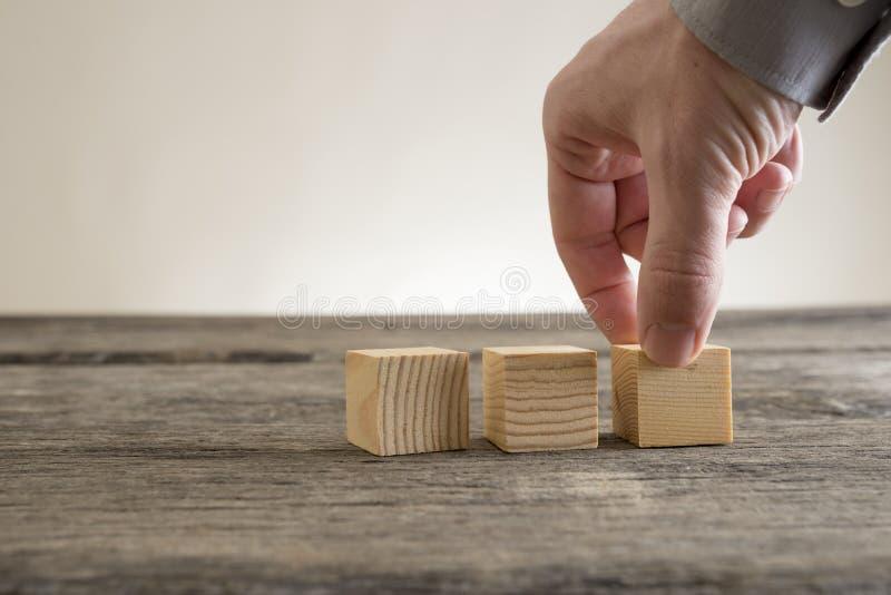 Três blocos vazios de madeira que estão sendo colocados em uma tabela rústica fotos de stock royalty free