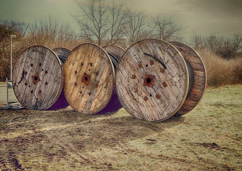 Três bobinas de madeira com cabos pretos fotografia de stock royalty free
