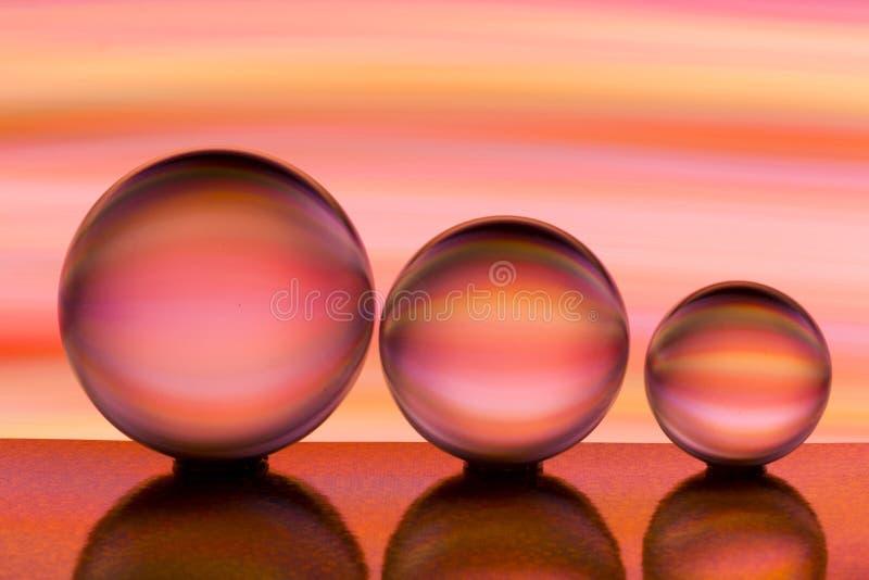Três bolas de cristal de vidro em seguido com um arco-íris da pintura clara colorida atrás deles imagem de stock
