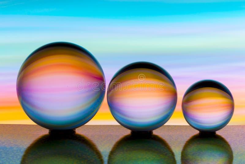 Três bolas de cristal de vidro em seguido com um arco-íris da pintura clara colorida atrás deles imagens de stock royalty free