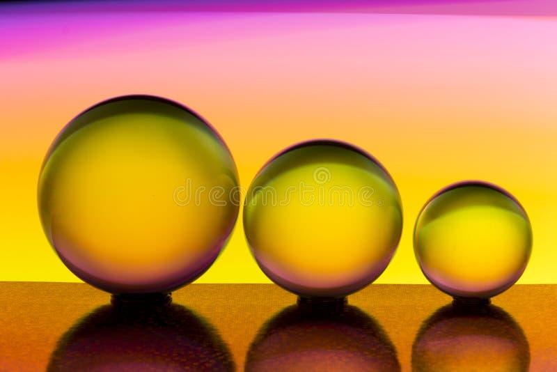 Três bolas de cristal de vidro em seguido com um arco-íris da pintura clara colorida atrás deles fotos de stock royalty free