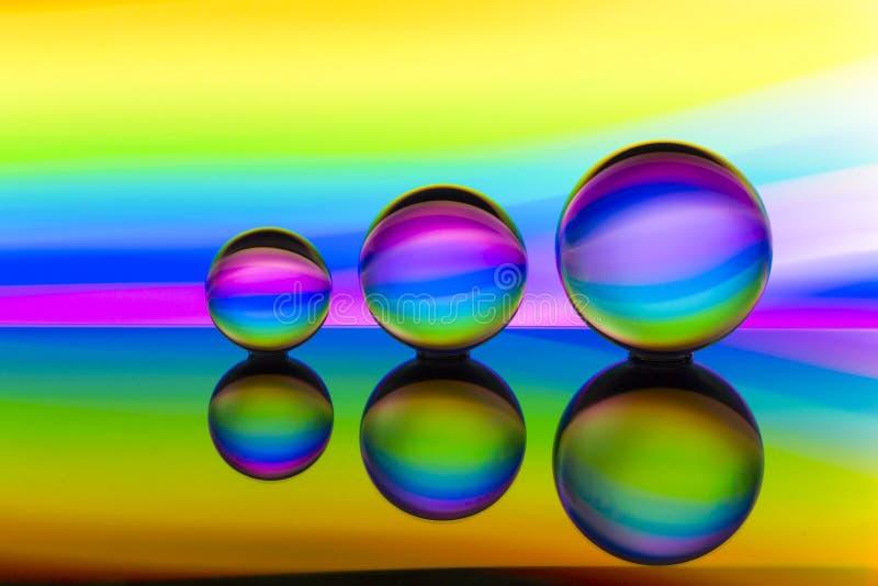 Três bolas de cristal de vidro em seguido com um arco-íris da pintura clara colorida atrás deles fotos de stock