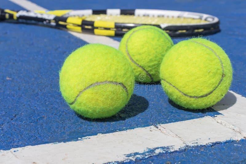 Três bolas de tênis e uma mentira da raquete na corte dura fotos de stock royalty free