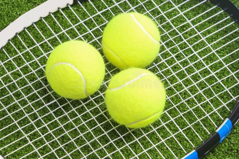 Três bolas de tênis encontram-se em cordas de uma raquete de tênis. sobre o la verde imagem de stock