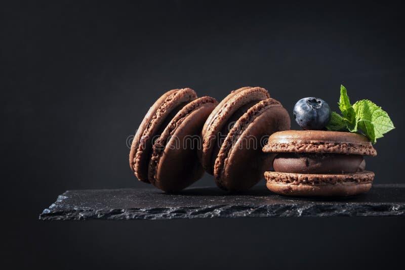 Três bolinhos de amêndoa do chocolate, baga azul e fim da hortelã acima no prato de pedra no preto fotos de stock royalty free