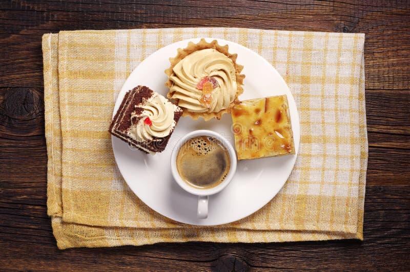 Três bolos e copos de café imagem de stock