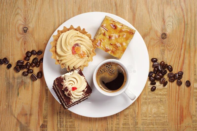 Três bolos e copos de café fotografia de stock