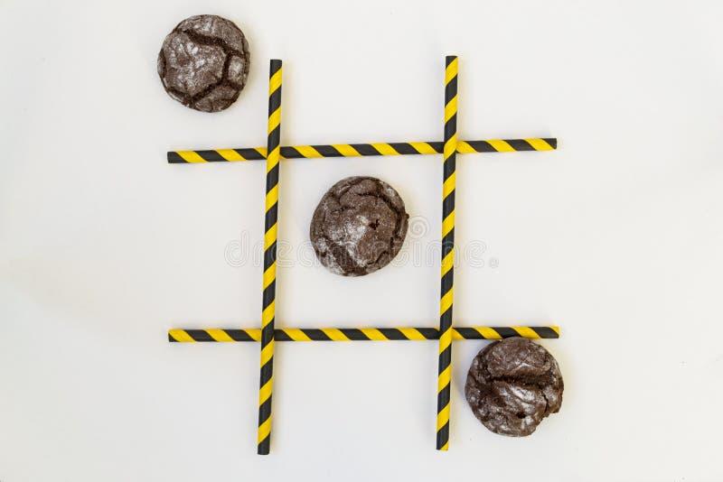 Três bolos marrons da pastelaria estão em seguido em um jogo do tique-TAC-dedo do pé, em uma grade em um fundo branco A grade con imagens de stock