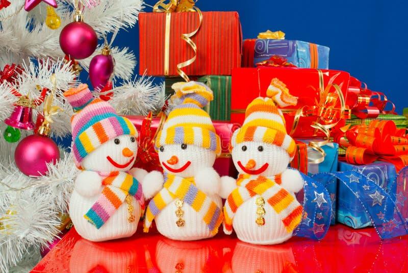 Três bonecos de neve na frente dos presentes de Natal fotografia de stock royalty free