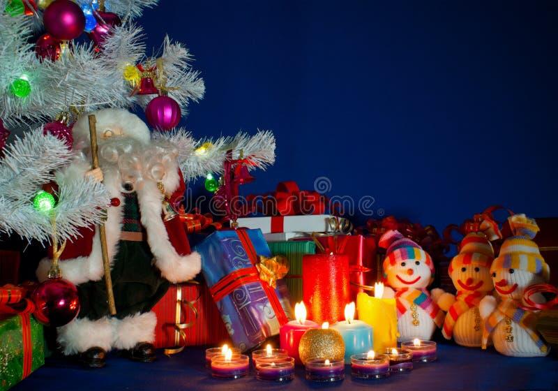 Três bonecos de neve na frente dos presentes de Natal fotos de stock