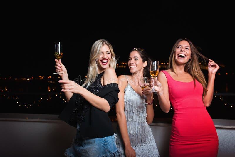 Três bonitos, mulheres alegres que têm uma noite das meninas para fora, tendo o divertimento fotografia de stock