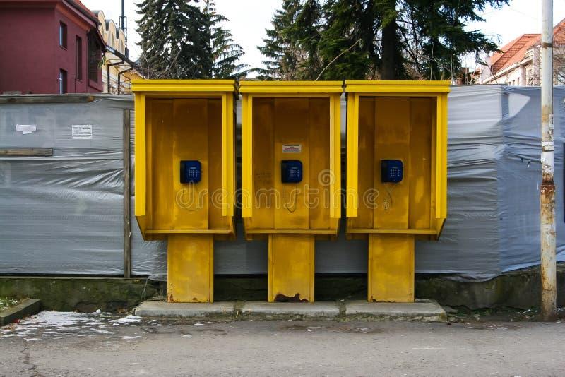 Três boothes amarelos do telefone com telefones azuis foto de stock royalty free