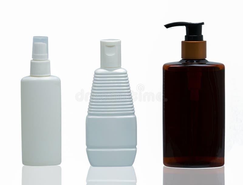 Três brancos e garrafas cosméticas plásticas marrons fotos de stock