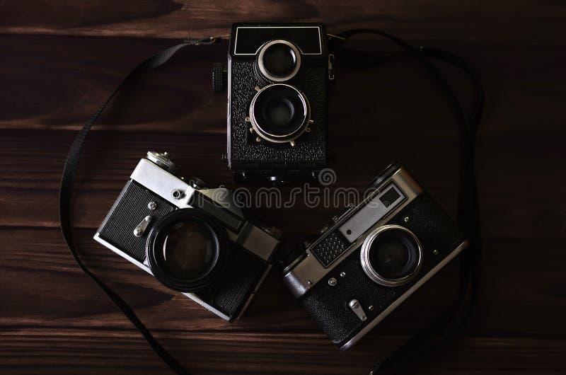 Três câmeras velhas do vintage em uma tabela de madeira fotos de stock