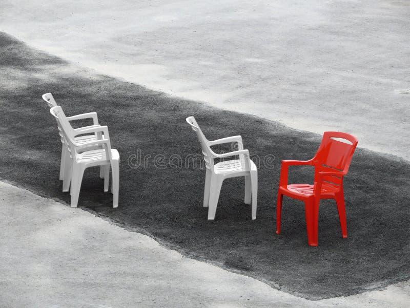 Três cadeiras brancas e um vermelho no asfalto escuro fotos de stock royalty free