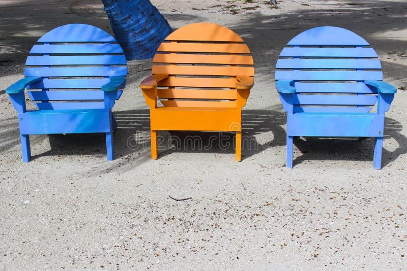 Três cadeiras de praia coloridas brilhantes na areia com cópia inferior s foto de stock royalty free