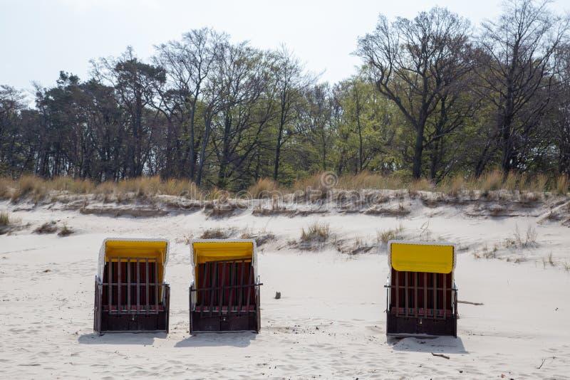 Três cadeiras de praia sós na praia de Zempin na ilha Usedom fotos de stock royalty free