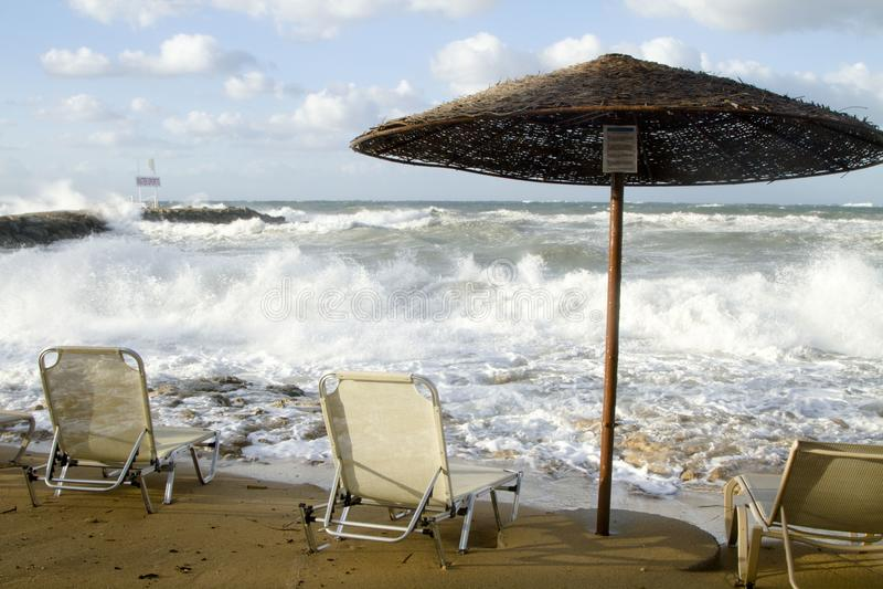 Três cadeiras e um dossel do sol em uma praia tormentoso foto de stock royalty free