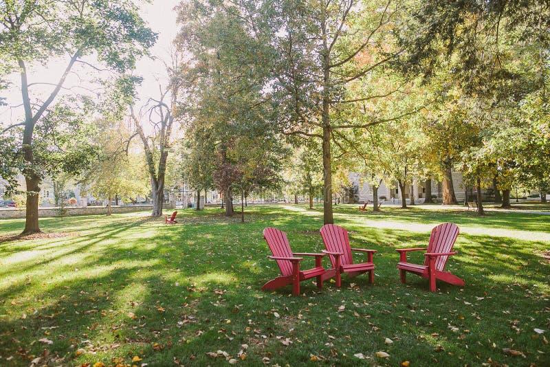 Três cadeiras vermelhas no parque imagem de stock