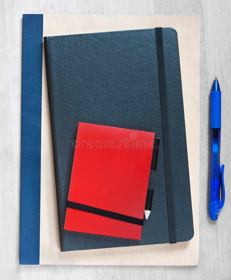 Três cadernos vazios em uma mesa de madeira do escritório ou da casa, com espaço da cópia para o texto fotografia de stock royalty free